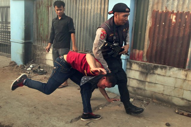An armed police officer arrests a demonstrator following clashes between police and demonstrators protesting against government plans to increase fuel prices in Makassar, South Sulawesi province, on November 7, 2014. The new Indonesian President Joko Widodo, known as Jokowi, is expected to announce a large increase in the price of petrol and diesel in the coming weeks to cut government subsidies that are a drain on Southeast Asia's biggest economy. (Photo by Yusuf Wahil/AFP Photo)