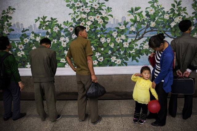 A girl holds a red balloon as she and others wait for a train at a subway station visited by foreign reporters during a government organised tour in Pyongyang, North Korea October 9, 2015. (Photo by Damir Sagolj/Reuters)