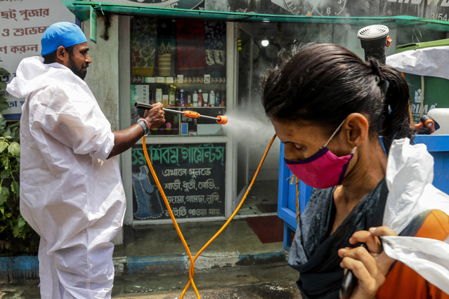 A civic worker sprays sanitizers in front of a shop as a woman wearing face mask walks past in Kolkata, India, Sunday, August 30, 2020. India has the third-highest coronavirus caseload after the United States and Brazil, and the fourth-highest death toll in the world. (Photo by Bikas Das/AP Photo)