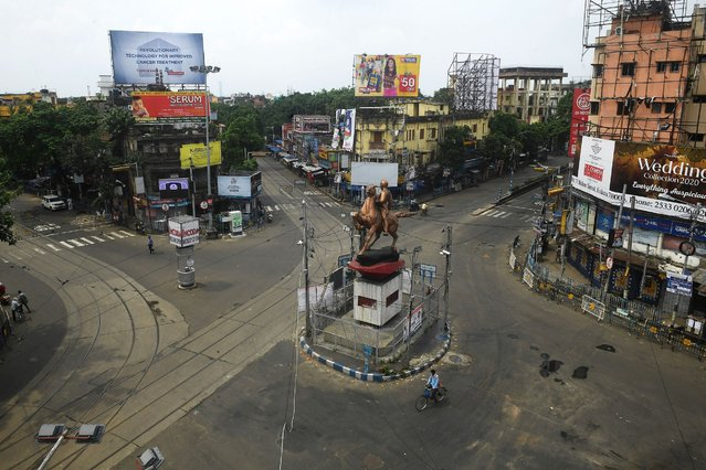 People cross a deserted intersection during a day long state-imposed lockdown as a preventive measure against the surge in Covid-19 coronavirus cases, in Kolkata on August 31, 2020. India on August 30 set a coronavirus record when it reported 78,761 new infections in 24 hours the world's highest single day rise even as it continued to open up the economy. (Photo by Dibyangshu Sarkar/AFP Photo)