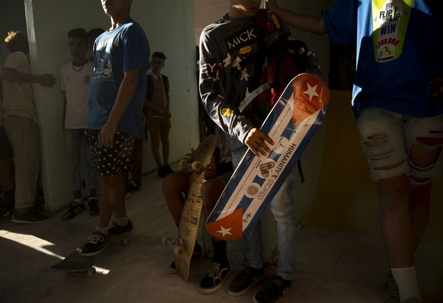 """In this January 11, 2018 photo, a skater carries a new Cuban flag motiffed skateboard, donated by Humanity Stoked, during the inauguration a new recreational space for skateboarders, created out of an abandoned gym at the Educational complex Ciudad Libertad, a former military barracks that the late Fidel Castro turned into a school complex after the revolution in Havana, Cuba. """"It means a lot that spaces like this are created, that it hasn't remained a hidden urban sport"""", said Hector Jorge, a 31-year-old skateboard aficionado. (Photo by Ramon Espinosa/AP Photo)"""