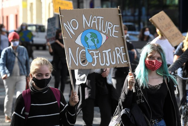 """Demonstrators hold a sign as Fridays for Future activists protest calling for a """"Global Day of Climate Action"""" in Hamburg, Germany, September 25, 2020. (Photo by Fabian Bimmer/Reuters)"""