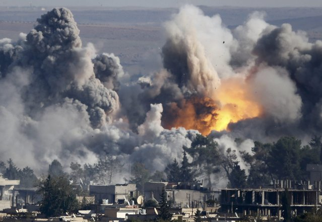 Smoke rises over Syrian town of Kobani after an airstrike, as seen from the Mursitpinar border crossing on the Turkish-Syrian border in the town of Suruc in this file October 18, 2014 file photo. A U.S.-led military coalition has been bombing Islamic State fighters who hold a large swathe of territory in both Iraq and Syria, two countries involved in complex multi-sided civil wars in which nearly every country in the Middle East has a stake. (Photo and caption by Kai Pfaffenbach/Reuters)