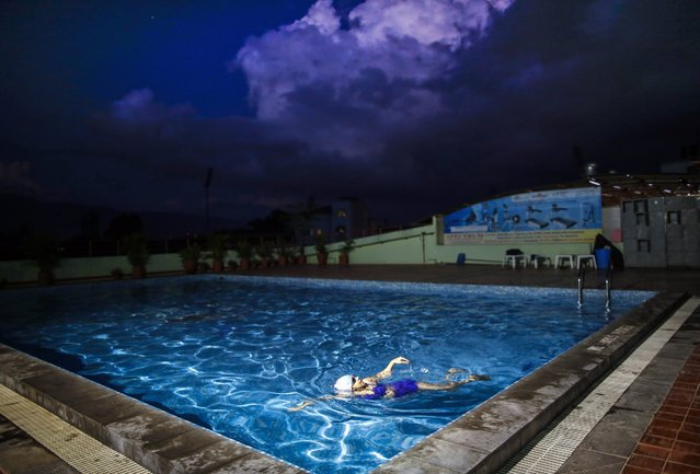"""A swimming enthusiast enjoys a late swim in private pool in Kathmandu, Nepal, on 27 September 2016 afternoon, during the end of the summer season in Nepal. While still measuring daytime temperatures of up to 30 degrees Celsius, the Department of Hydrology and Meteorology of the Government of Nepal expects """"light rain likely to occur at a few places of the eastern and western regions and at one or two places of the central region"""", in a forcast on 27 September. (Photo by Narendra Shrestha/EPA)"""