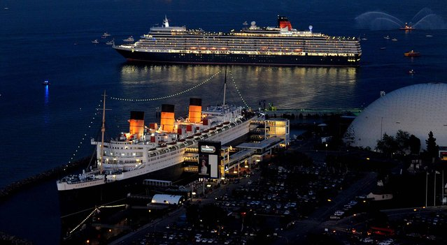 Cunard's ocean liner Queen Elizabeth meets her docked sister ship Queen Mary in Long Beach, California, on March 12, 2013.  This is the Queen Mary's first encounter with a Queen Elizabeth since 1967 when the Queen Mary, during her final transatlantic crossing, passed by the original Queen Elizabeth. (Photo by John Shearer/Invision for Cunard)