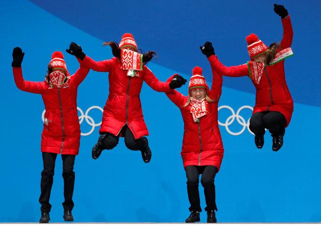 Belarus' gold medallists Nadezhda Skardino, Iryna Kryuko, Dzinara Alimbekava and Darya Domracheva celebrate on the podium during the medal ceremony for the biathlon Women' s 4x6 km Relay at the Pyeongchang Medals Plaza during the Pyeongchang 2018 Winter Olympic Games in Pyeongchang on February 23, 2018. (Photo by Kim Hong-Ji/Reuters)