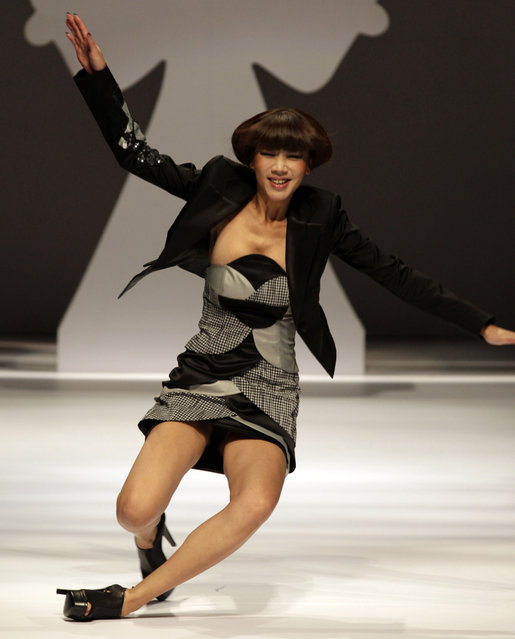 A model falls while displaying a design from Wu Xuewei and Wu Xuekai, winners of the Asahi Kasei China Fashion Designer Award during China Fashion Week held in Beijing, China, Friday, October 29, 2010. (Photo by Ng Han Guan/AP Photo)