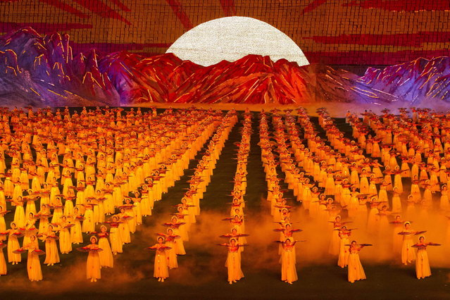 North Koreans dance and flip colored cards to form a giant image in the seats of a stadium during an Arirang mass games performance in Pyongyang, North Korea, on Sunday, September 9, 2012. (Photo by David Guttenfelder/AP Photo)