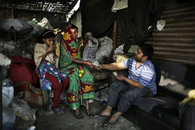 In this November 6, 2014 photo, Munna bhai, a trash dealer, hands over money to Marjina for trash she segregated, as her daughter Murshida eats sweet lemon on the outskirts of New Delhi, India. The family spends their day at a landfill picking through other people's garbage to find salvageable bits to resell or recycle, earning $26 a month. (Photo by Altaf Qadri/AP Photo)
