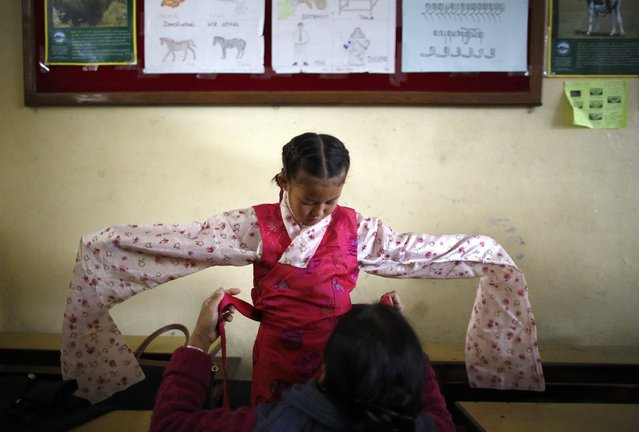 A Tibetan girl gets help from her mother as she gets dressed for an event  organised by the Tibetan Refugee Community in Nepal commemorating the 25th Anniversary of the Nobel Peace Prize conferment to exiled Tibetan spiritual leader Dalai Lama and the 66th International Human Rights Day in Kathmandu December 10, 2014. (Photo by Navesh Chitrakar/Reuters)