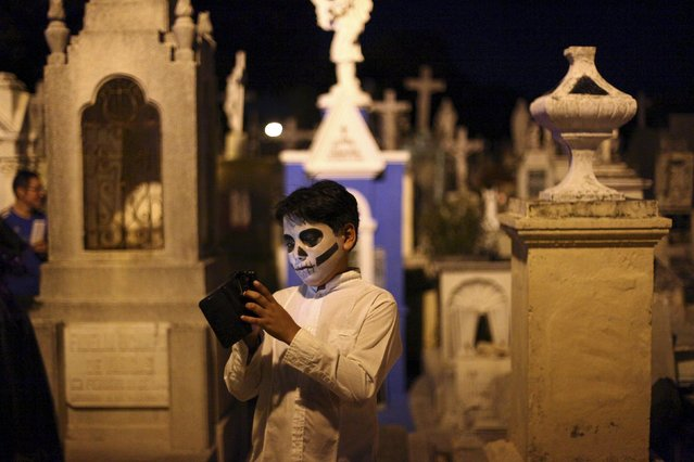 "A child, with his face painted as a skull, uses his cellphone while waiting for the traditional parade called ""Paseo de las Animas"", or Parade of Souls, as part of Day of the Dead celebrations in Merida, Mexico, October 31, 2015. (Photo by Lorenzo Hernandez/Reuters)"