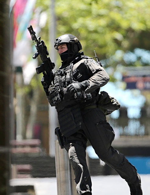 """An armed police officer runs along the street close to a cafe under siege at Martin Place in the central business district of Sydney, Australia, Monday, December 15, 2014. A hostage situation erupted inside a chocolate shop and cafe in Australia's largest city on Monday, with the nation's prime minister saying it may be """"politically motivated"""". (Photo by Rob Griffith/AP Photo)"""