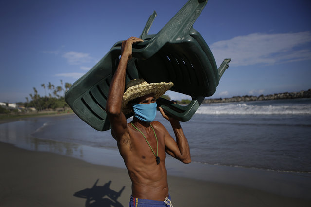 Douglas Yriarte carries rental chairs for tourists on the La Ultima beach which was closed for months amid the COVID-19 pandemic in La Guaira, Venezuela, Friday, October 23, 2020. (Photo by Matias Delacroix/AP Photo)