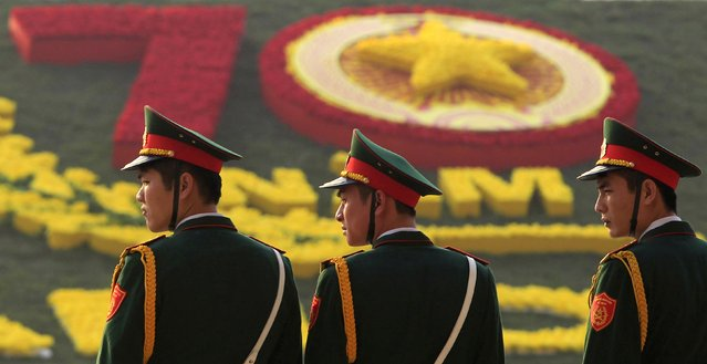 Soldiers stand in front of a floral decoration during celebrations to commemorate the 70th anniversary of the establishment of the Vietnam People's Army at the National Convention Center in Hanoi December 20, 2014. The Vietnam People's Army was founded on December 22, 1944 and led by General Vo Nguyen Giap in Cao Bang province, initially with only 34 members. (Photo by Reuters/Kham)