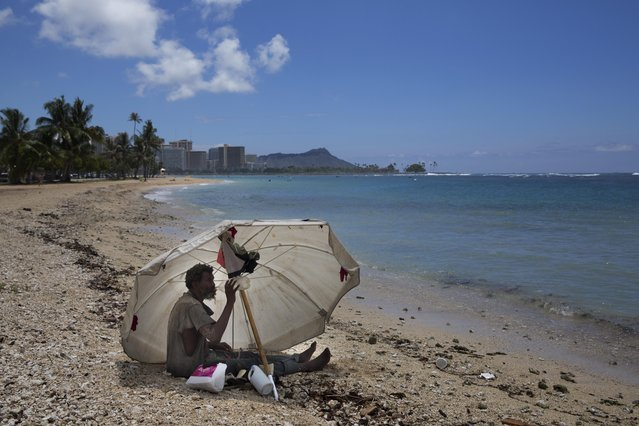 In this Thursday, August 27, 2015 photo, a homeless man drinks water while sitting on the beach at Ala Moana Beach Park located near Waikiki in Honolulu. Homelessness in Hawaii has grown steadily in recent years, leaving the state with the nation's highest rate of homeless people per capita. (Photo by Jae C. Hong/AP Photo)