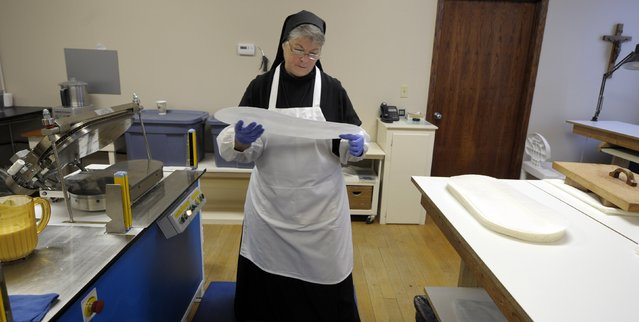 Sister Rebecca Leis inspects a baked sheet of low-gluten alter bread at the Benedictine Sisters of Perpetual Adoration monastery in Clyde Missouri December 18, 2014. (Photo by Dave Kaup/Reuters)