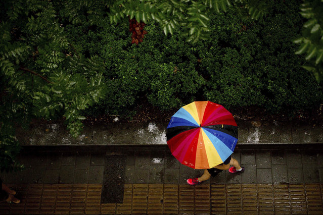 A woman carries a rainbow-colored umbrella as she walks during a rain shower in Beijing, Thursday, August 18, 2016. Although Beijing is in a semi-dry climate, it receives much of its annual precipitation during the summer months. (Photo by Mark Schiefelbein/AP Photo)