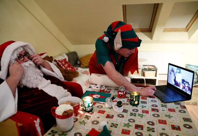 An assistant helps Pal Pillmayer, dressed as Santa Claus, as he prepares to interact with children by video chat, amid the coronavirus disease (COVID-19) outbreak in Budapest, Hungary, November 30, 2020. (Photo by Bernadett Szabo/Reuters)