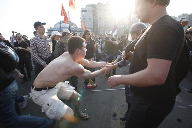 In this photo taken Sunday, May 6, 2012, Denis Lutskevich, left, is detained by police during an opposition rally in Bolotnaya Square in Moscow.  A former naval cadet and first-year student, 21-year-old Lutskevich was attending his first protest when he was detained, and is still in prison Monday May 6, 2013, on the first year anniversary of the protest. Lutskevich is one of more than two dozen people who are still held, facing criminal charges over the involvement in the May 6, 2012 opposition protest that ended in violent clashes between demonstrators and police. (AP Photo/Pavel Golovkin)