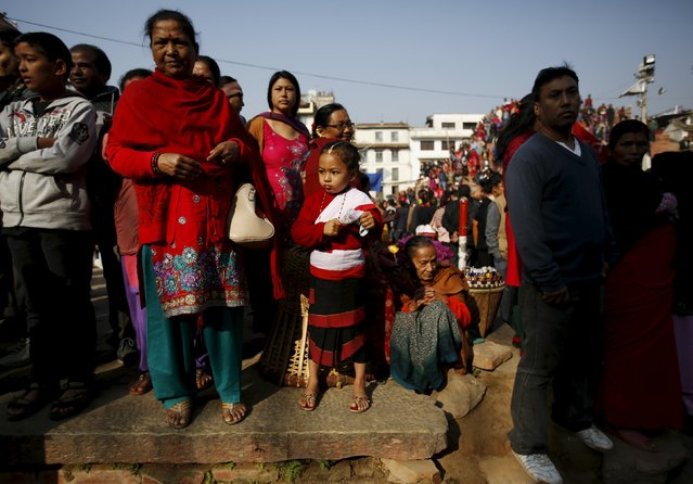 A Newari girl (C), dressed in traditional attire, observes the Newari New Year parade that falls during the Tihar festival, also called Diwali, in Kathmandu, Nepal November 12, 2015. (Photo by Navesh Chitrakar/Reuters)