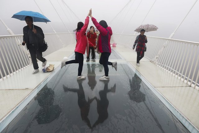 Tourists take pictures on the Zhangjiajie Grand Canyon Glass Bridge in Zhangjiajie City, Hunan Province, central China, 20 October 2016. Claimed by China to be the longest and highest glass bridge in the world, the tourist attraction measures 430 meters long, 6 meters wide and is suspended some 300 meters above ground. The floor of the bridge is made of 99 pieces of reinforced glass. (Photo by v/EPA)