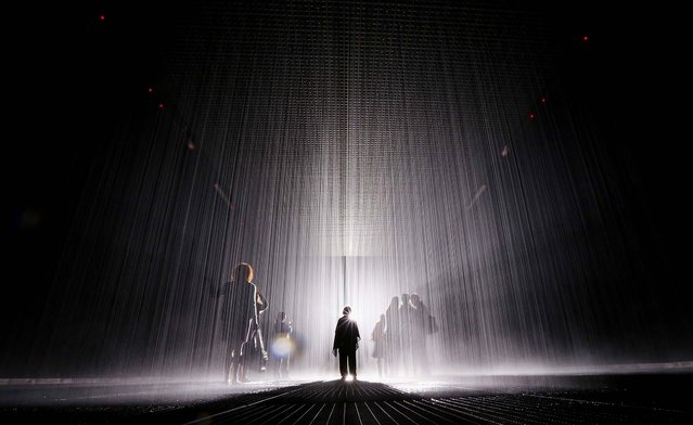 "Visitors gather in the new ""Rain Room"" installation at the Museum of Modern Art (MoMA) in Manhattan, on May 15, 2013. The 5,000 square-foot installation creates a field of falling water that stops in the area where people walk through, allowing them to remain dry. The piece, created by Random International, releases a 260-gallon per minute shower around visitors. (Photo by Mario Tama/Getty Images)"
