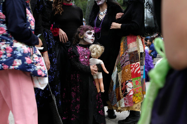 "Nina, 5, dressed as a ""Catrina"", or skeleton lady waits with her mother for the start Gran Procession of the Catrinas, to mark the upcoming Day of the Dead holiday, in Mexico City, Sunday, October 23, 2016. (Photo by Anita Baca/AP Photo)"