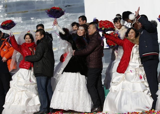Couples pose for their wedding photographs after a group wedding ceremony which was held as part of the Harbin International Ice and Snow Festival in the northern city of Harbin, Heilongjiang province January 6, 2015. (Photo by Kim Kyung-Hoon/Reuters)