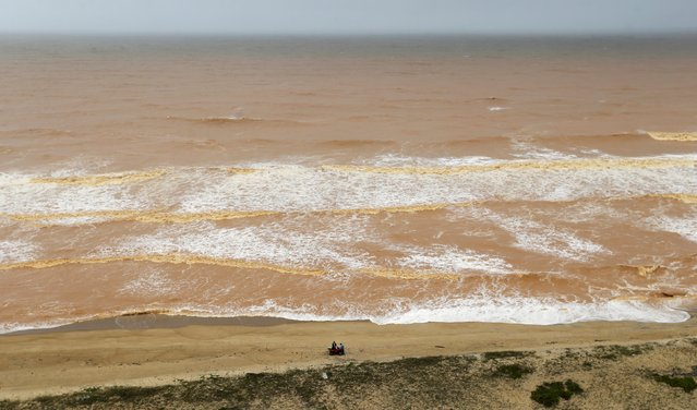 Men stand on the beach near the mouth of Rio Doce (Doce River), which was flooded with mud after a dam owned by Vale SA and BHP Billiton Ltd burst, as the river joins the sea on the coast of Espirito Santo in Povoacao Village, Brazil, November 22, 2015. (Photo by Ricardo Moraes/Reuters)