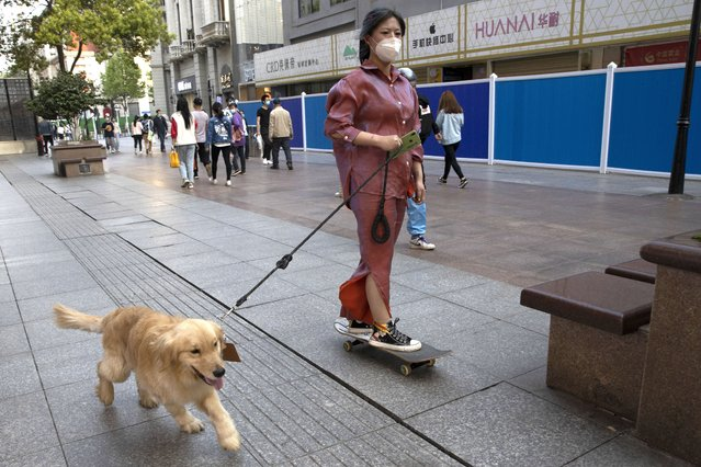 A resident gets a ride from her dog along a retail street in Wuhan in central China's Hubei province, Thursday, April 9, 2020. (Photo by Ng Han Guan/AP Photo)