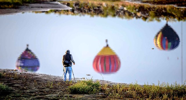 A photographer takes a snapshot of the reflection of balloons as they take off from Balloon fiesta park in Corrales, N.M., near a north diversion channel reservoir Wednesday, October 7, 2015. (Photo by Roberto E. Rosales/Albuquerque Journal via AP Photo)