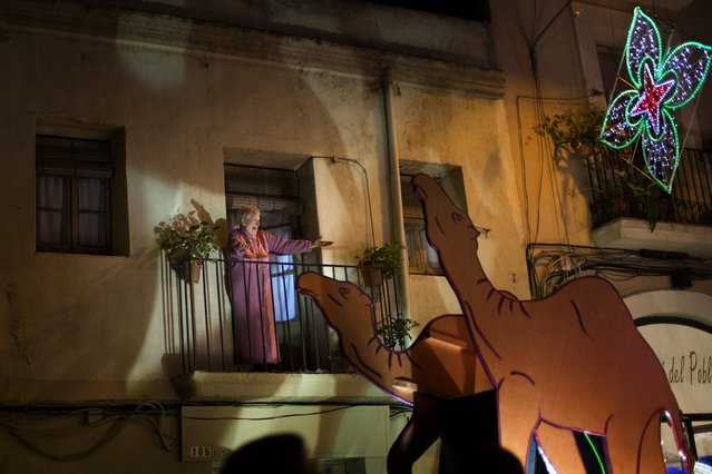 """A woman reacts as one of the Three Wise Men passes by her balcony during the """"Cabalgata de Reyes"""", or the Three Wise Men parade in Barcelona, Spain, Monday, January 5, 2014. The traditional parade marks the eve of the Epiphany, a Christian holiday celebrating the story of the three wise men believed to have followed a bright star to offer gifts of gold, frankincense and myrrh to the newborn Jesus in Bethlehem. (Photo by Emilio Morenatti/AP Photo)"""