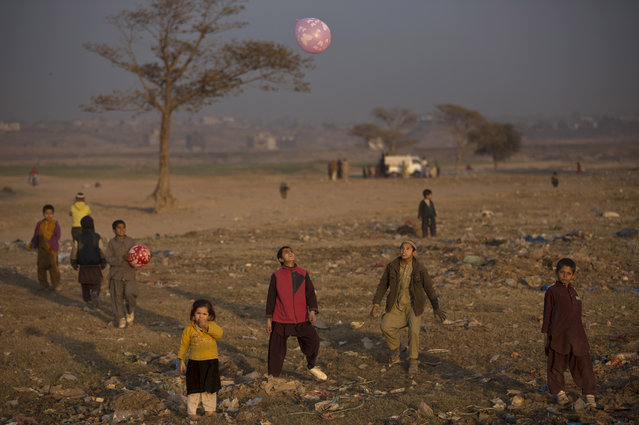Afghan refugee children play in a field near a slum where they live on the outskirts of Islamabad, Pakistan, Friday, January 2, 2015. (Photo by Muhammed Muheisen/AP Photo)