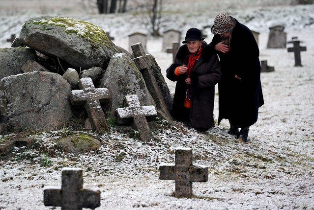 Elderly women visit a German World War One military cemetery during the All Saints' Day in the village of Baruny, some 110 km northwest of Minsk, on November 1, 2016. (Photo by Sergei Gapon/AFP Photo)