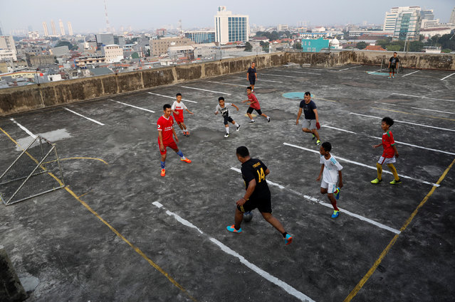 Local residents play soccer on the top floor of a parking garage in Jakarta, Indonesia, May 4, 2018. (Photo by Darren Whiteside/Reuters)