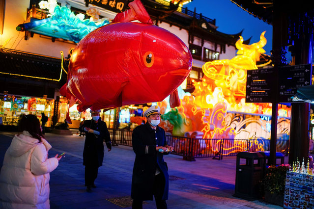 Security guards wearing face masks carry a giant balloon in the shape of a fish ahead of the Chinese Lunar New Year festivity at Yu Garden, following the coronavirus disease (COVID-19) outbreak in Shanghai, China on January 29, 2021. (Photo by Aly Song/Reuters)