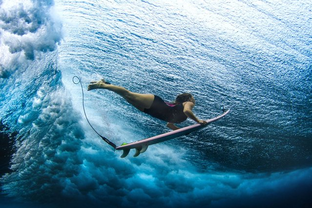 A surfer avoids a huge wave above her head. (Photo by Sarah Lee/Caters News)