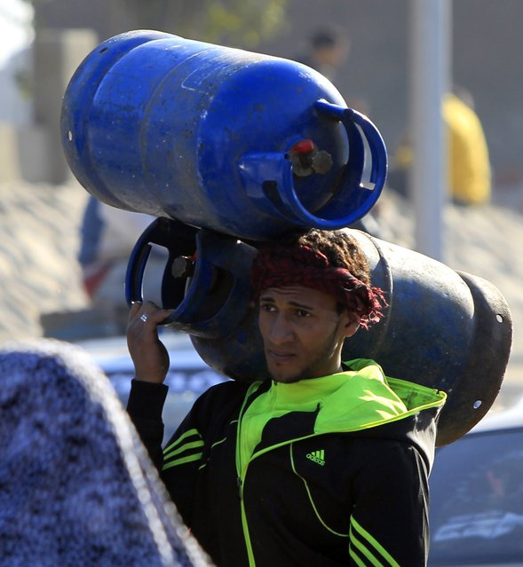 A man carries gas cylinders to be refilled  at a distribution point in Cairo January 19, 2015. (Photo by Mohamed Abd El Ghany/Reuters)