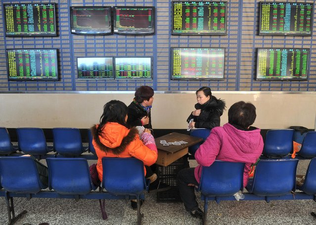 Investors play cards in front of a screen showing stock information at a brokerage house in Hefei, Anhui province, January 19, 2015. (Photo by Reuters/Stringer)