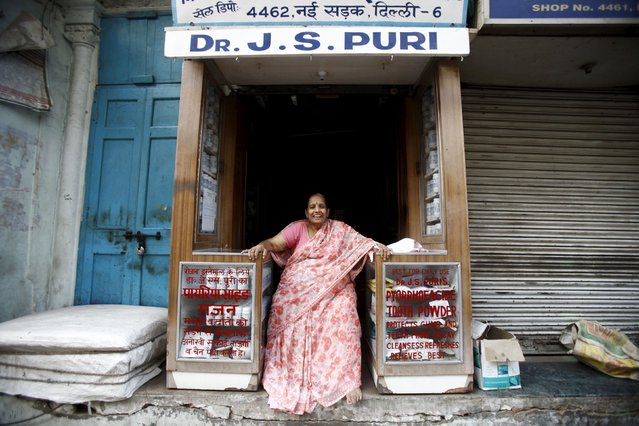 A woman selling tooth powder smiles while sitting at her shop in the old quarters of Delhi in this April 10, 2013 file photo. India is expected to release inflation data this week. (Photo by Mansi Thapliyal/Reuters)
