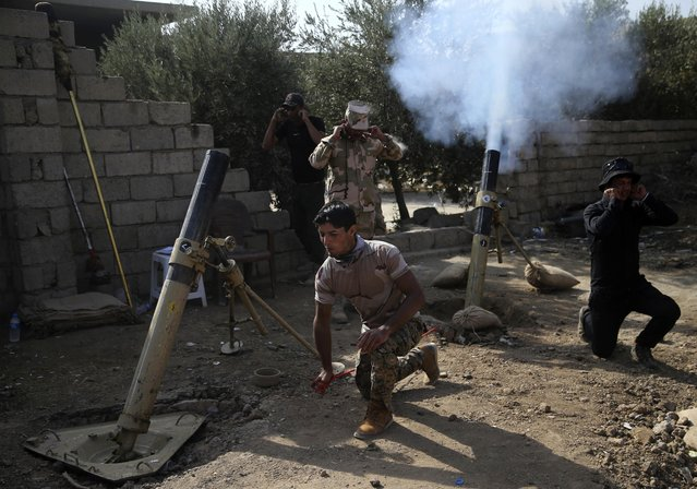 Iraqi army soldiers fire mortars against the Islamic State militants, at Shahrazad village 2 miles (3 kilometers) east of Mosul, Iraq, Monday, November 14, 2016. A suicide bombing in Iraq targeted the Shiite sacred city of Karbala on Monday, killing at least six civilians, the latest attempt by the Islamic State group to distract from the government forces' offensive on the IS-held northern city of Mosul. (Photo by Hussein Malla/AP Photo)