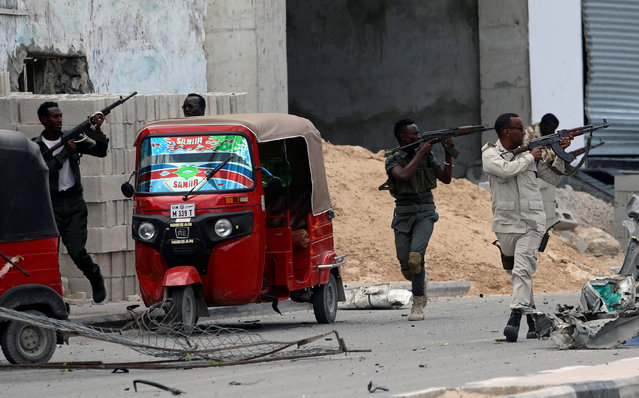 Somali security agents take position as they secure the scene of a suicide car bombing near Somalia's presidential palace in Mogadishu, Somalia July 7, 2018. (Photo by Feisal Omar/Reuters)