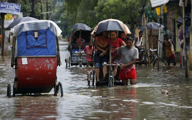 A rickshaw driver pushes his rickshaw carrying women through a waterlogged street in Gauhati, India, Tuesday, July 16, 2013. (Photo by Anupam Nath/AP Photo)