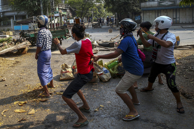 Anti-coup protesters armed with sling-shot and empty glass bottle reacts to charging riot policemen in Mandalay, Myanmar, Tuesday, March 2, 2021. (Photo by AP Photo/Stringer)