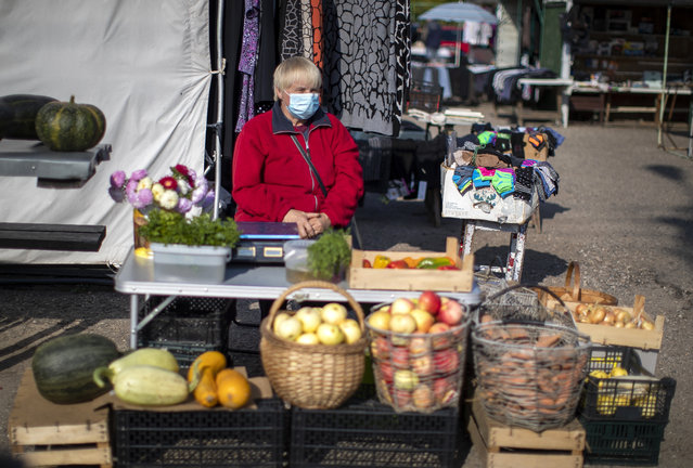 A vegetable vendor wearing a face mask to protect against coronavirus, waits for customers at the bazaar in the small town of Ignalina, some 110km (68.3 miles) north of the capital Vilnius, Lithuania, Saturday, September 26, 2020. (Photo by Mindaugas Kulbis/AP Photo)
