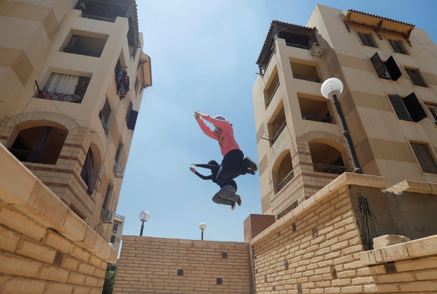 """Egyptian women from Parkour Egypt """"PKE"""" practice their parkour skills around buildings on the outskirts of Cairo, Egypt on July 20, 2018. Curious crowds, accustomed to women taking a low profile in Egypt, often congregate to watch the training, sometimes taking pictures and filming. But the women keep up the training unhindered, insisting that no sport is exclusive for men. (Photo by Amr Abdallah Dalsh/Reuters)"""