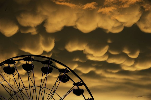 Mammatus clouds move over the Fredericksburg Agricultural Fair after a round of thunderstorms passed through the area on Thursday, August 1, 2013. Mammatus are most often associated with severe thunderstorms.  (Photo by Peter Cihelka/AP Photo/The Free Lance-Star)