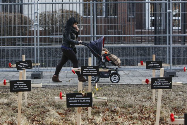A woman with a child walks past crosses with the names of victims who were killed in the shelling of the government-held port of Mariupol by pro-Russian rebels on January 24, during a protest against Russia's actions in Donetsk region in front of Russian embassy in Kiev, February 1, 2015. (Photo by Valentyn Ogirenko/Reuters)