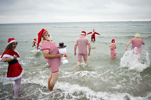 Participants of the 2015 World Congress of Santa Clauses take a bath at Bellevue beach north of Copenhagen, Denmark on July 21, 2015. (Photo by Erik Refner/AFP Photo)