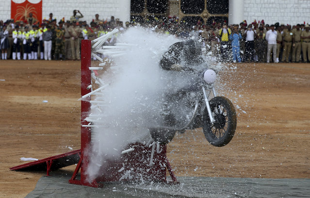 A member of ASC Tornados, the motorcycle display team of the Indian army, performs a stunt during Indian Independence Day celebrations in Bangalore, India, Wednesday, August 15, 2018. India won independence from British colonialists in 1947. (Photo by Aijaz Rahi/AP Photo)